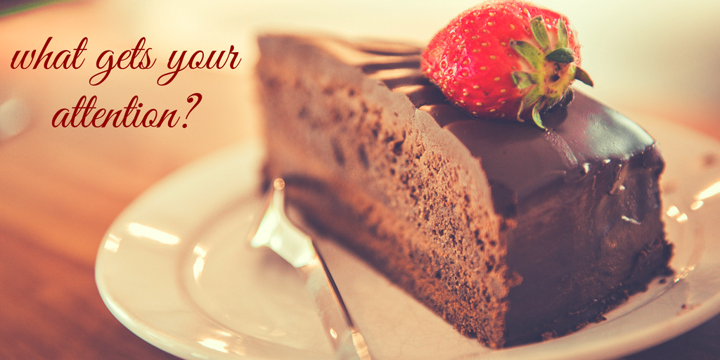 "large piece of chocolate cake with a strawberry on top, white plate, silver fork, wooden table ""What Gets Your attention?"""