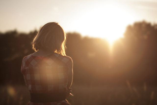 young woman in a plaid shirt watching the sunset from a field, gentleness