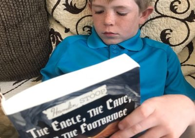 Robert and Sue's grandson Robby reading the fantasy book his granddad wrote!