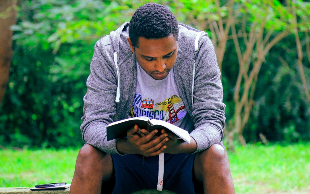 Christian-scriptures-man in San Francisco-shirt-reading-book-outside-bench-wisdom-college-students-Why You Should Read The Bible-rbs-blog-image_gift-habeshaw-699056-unsplash