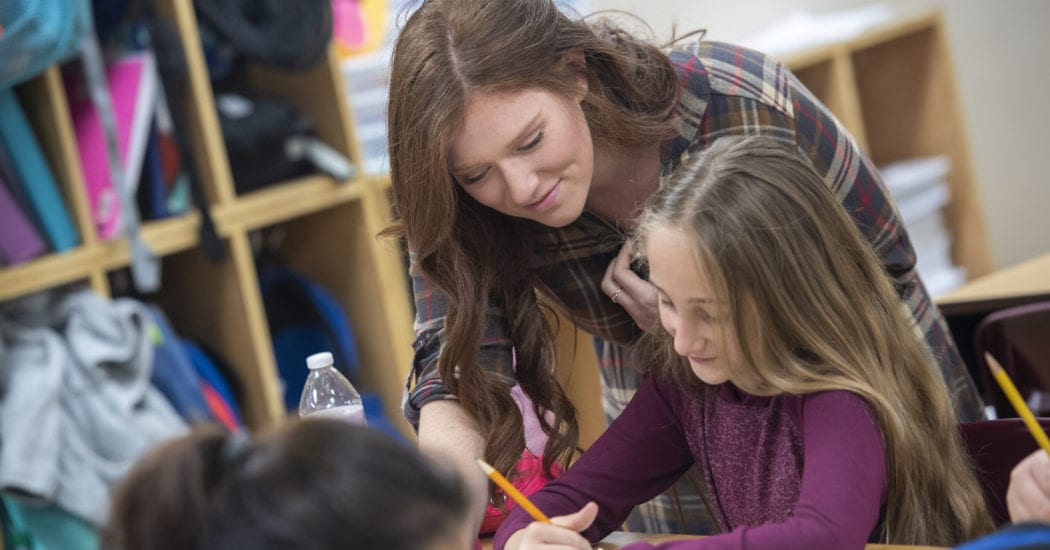 Student teachers helps elementary student at her desk.