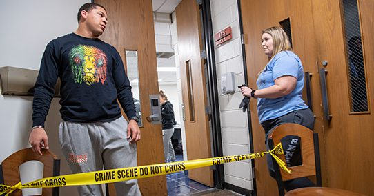 Students investigate a mock crime scene.