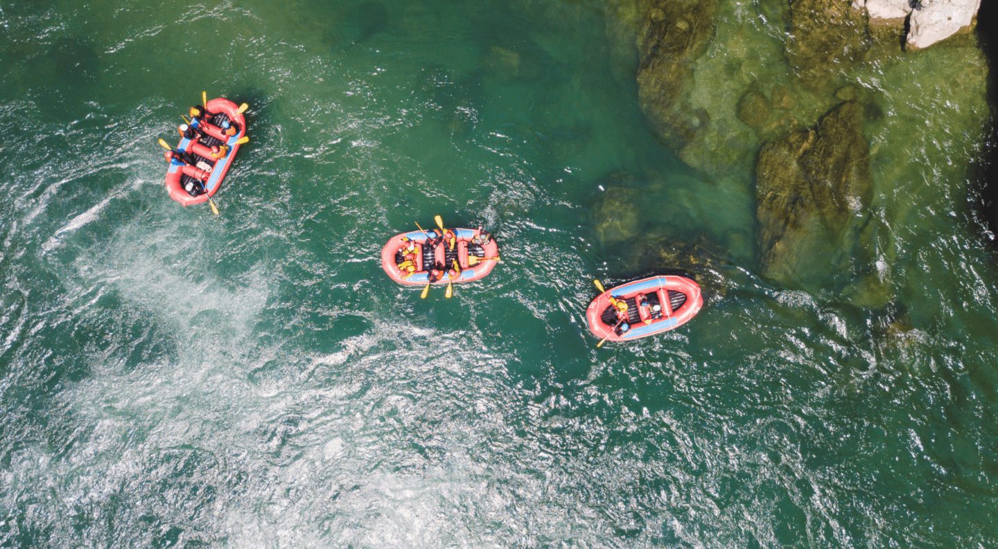 Aerial view of multiples rafting boats floating down the river