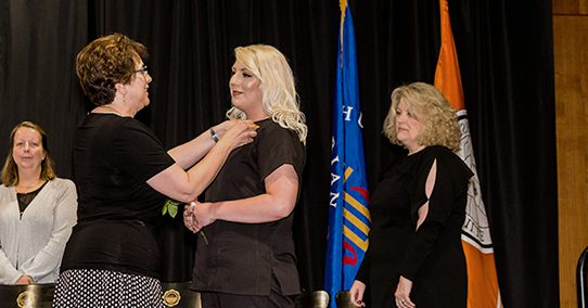 Nursing student receives her honorary pin for completing the nursing program.