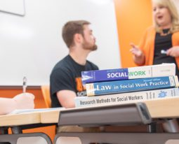 Students taking notes during a social work class.