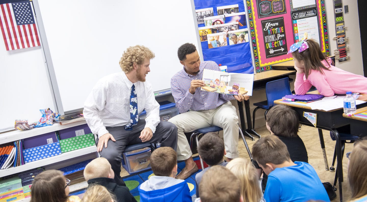 students reading to elementary class