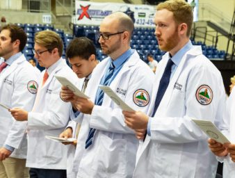 kycom students read the pledge while receiving their white coat of compassion