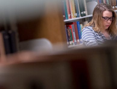 A UPIKE student sits studying on the second floor of the Allara Library