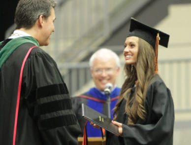 upike student greeted by university president dr. burton webb on stage at commencement