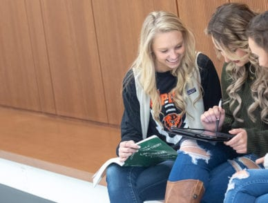 Students are pictured sitting in the health professions education building looking at photos on an ipad