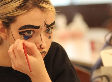 Student practices pop-art makeup during a stage make-up course.