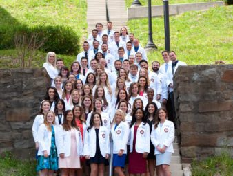 KYCO Class of 2021 students stand on the Historic 99 steps after receiving their white coats in April 2018