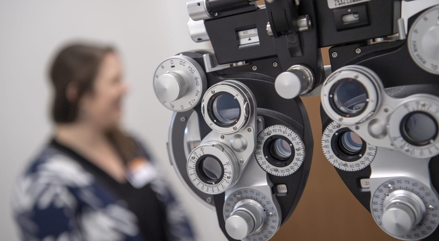 optometry equipment in the foreground with professor standing in the background