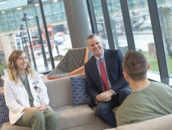 KYCO Dean Dr. Bacigalupi sitting with KYCO students in the student lounge.