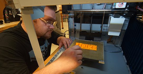 Student making the UPIKE logo on a 3D printer.
