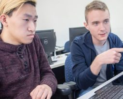 Two students working on computers during a computer science class.