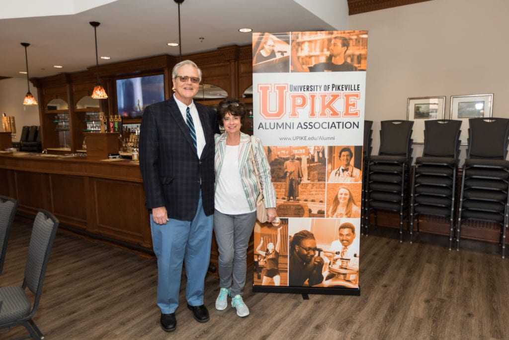 couple taking a photo in front of the UPIKE banner