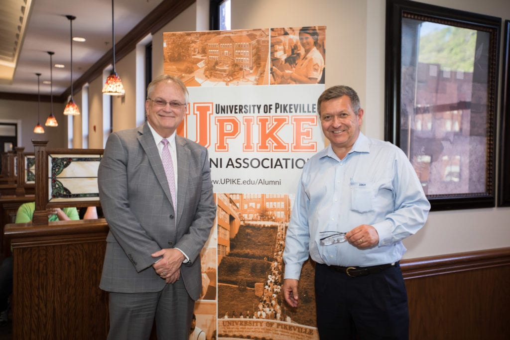 two guests in front of UPIKE banner