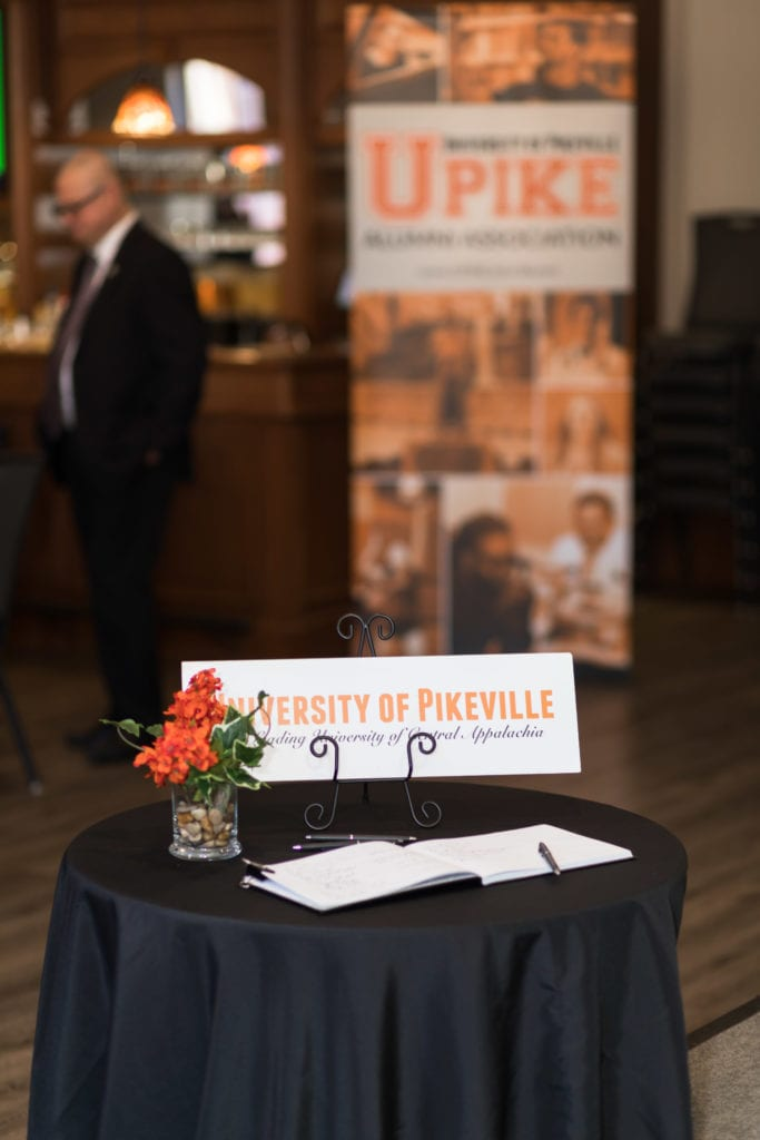 welcome table with a sign in book and UPIKE sign