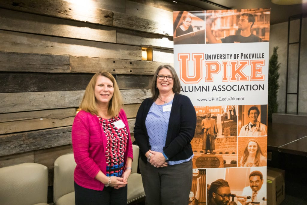Two ladies pose in front of UPIKE banner