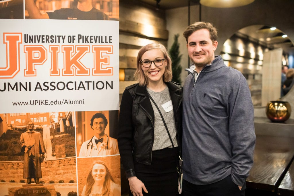 two guests pose in front of UPIKE banner