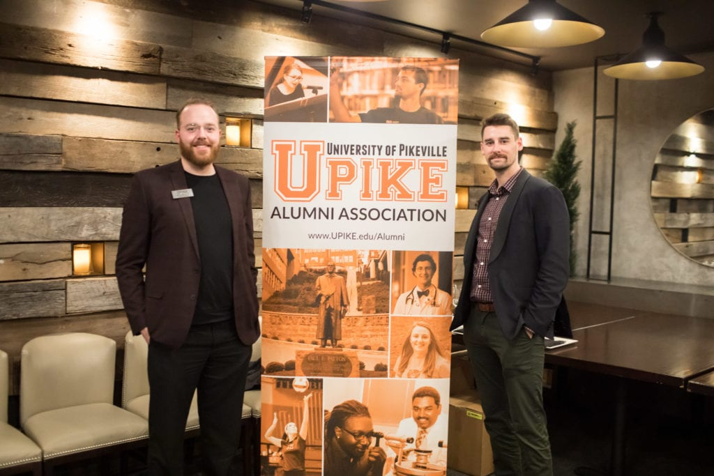 two guests pose for a photo in front of UPIKE banner