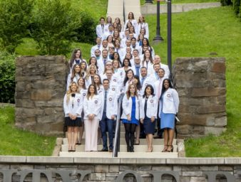 KYCO Class of 2021 pose in their symbolic white coats