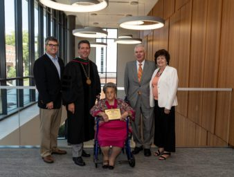 Eula holding award with Dr. Webb and Baird Family