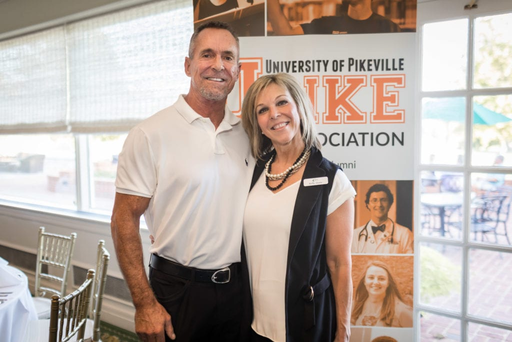 two event attendees pose for a photo in front of the UPIKE banner