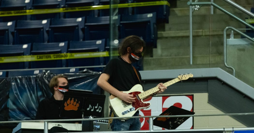 band student playing guitar at ballgame