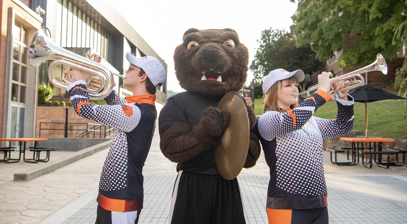 two band students and mascot in plaza