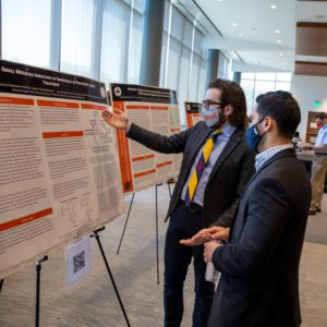 KYCOM student presenting their research poster to a fellow student.