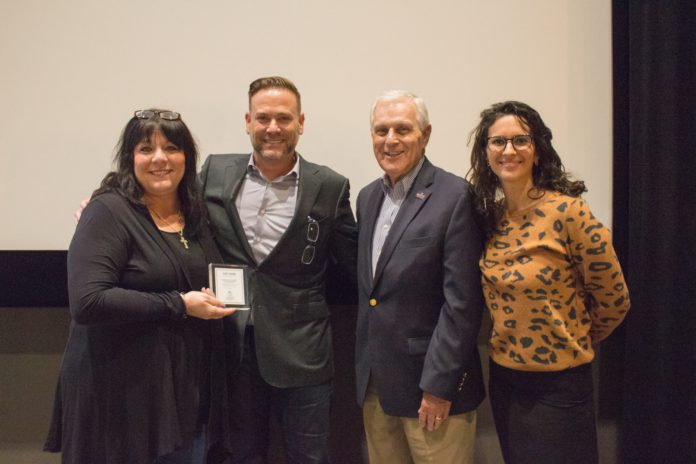 Clint Higham poses with Belmont University staff members after his presentation to students.