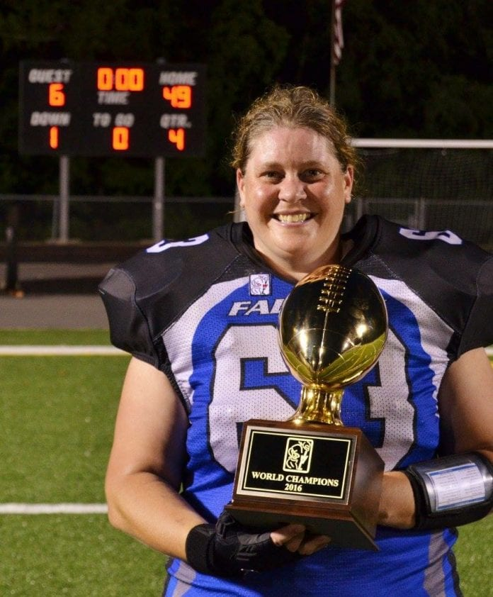 Nanney holding the world championship trophy from the independent women's football league