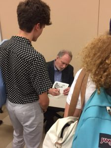 Dr. Harrington signing a student's copy of his book