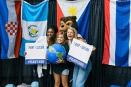 Students at the Study Abroad Fair holding signs of the places they want to travel to
