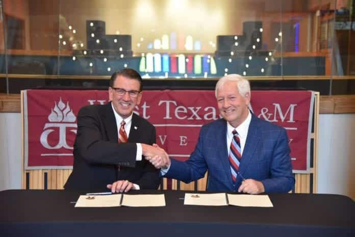 Both University presidents shake hands after signing the agreement between West Texas and Belmont.