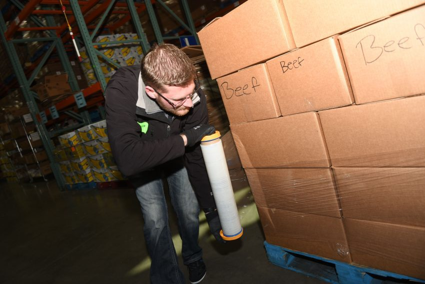 A staff member wraps a pallet with plastic wrap--ready for shipment!