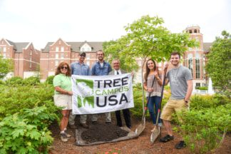 Students and staff pose for a picture in front of a sassafras tree and the USA Tree Campus sign.