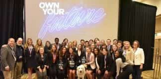 Students pose for a photo after DECA's award ceremony