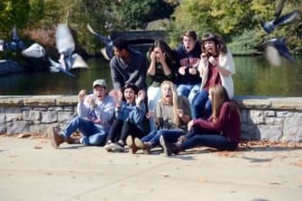 A group of students are 'photobombed' during an Admissions shoot at Centennial Park