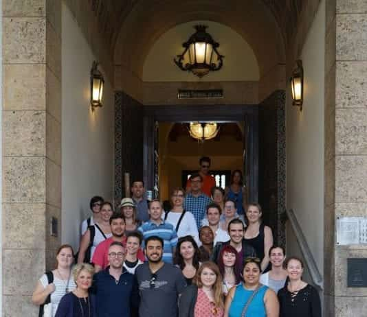 The Massey Alumni trip to Cuba participants pose in front of a historical building.