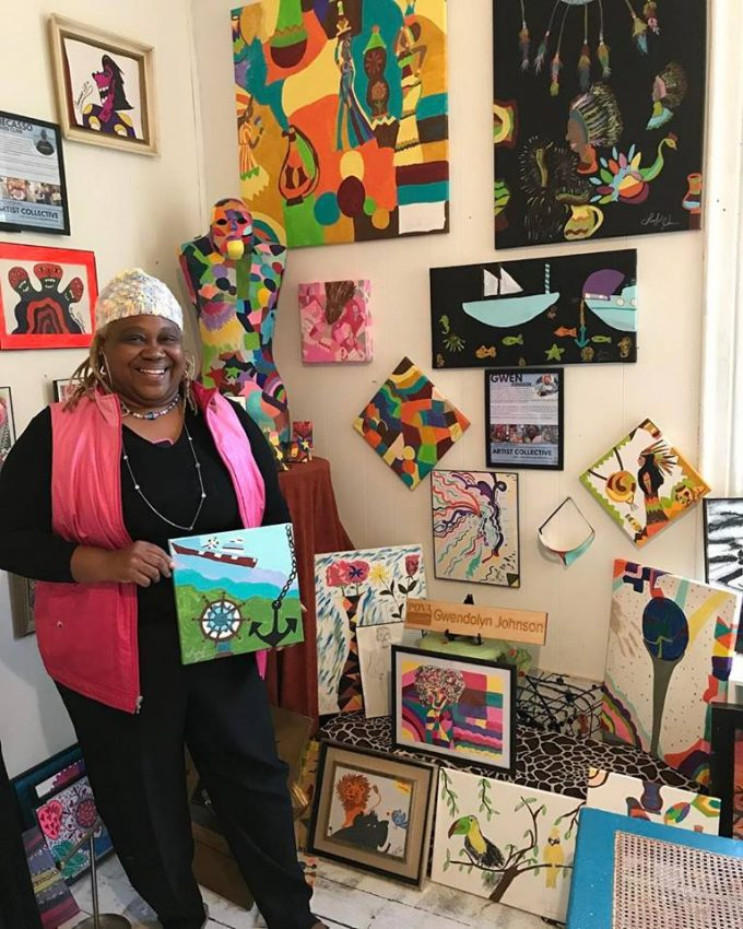 An artist showcases her piece--smiles proudly in front of the pieces she has created