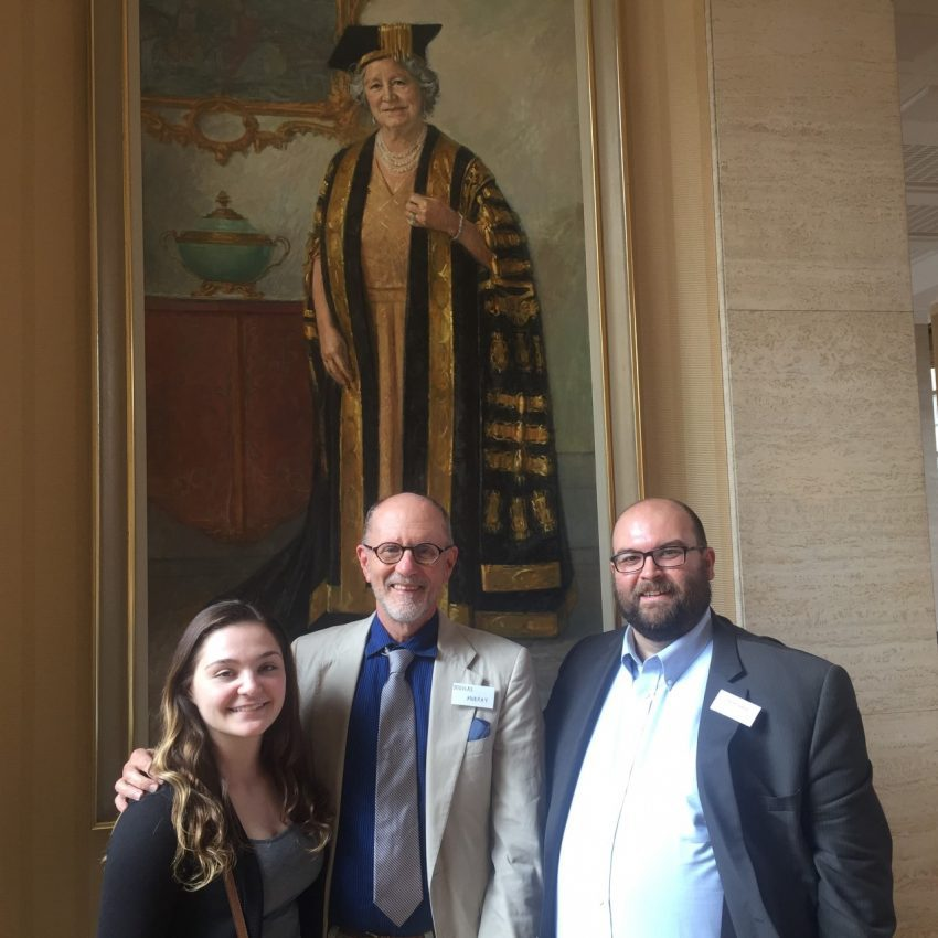 The three Belmont speakers stand in the Senate House of the University, in front of a portrait of the University's previous Chancellor, Queen Elizabeth, the Queen Mother.