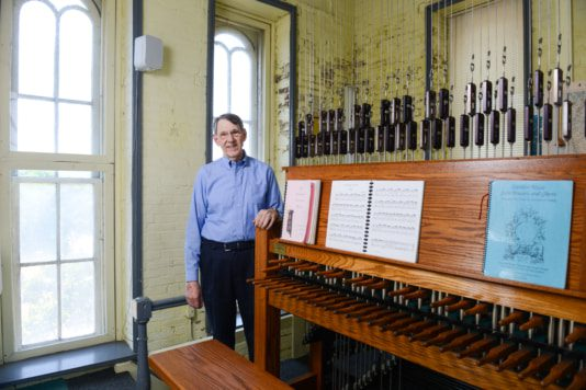 Dr. Richard Shadinger stands in front of the carillon in Belmont's Bell Tower.