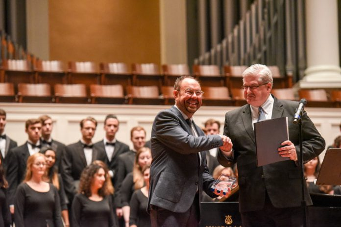 Sharp Receives his award from Dean of the College of Visual and Performing Arts Dr. Stephen Eaves on the stage of the McAfee Concert Hall.