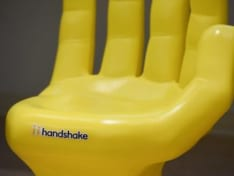yellow plastic chair shaped like a hand