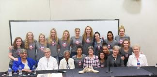 Members of the current BU Women's basketball team standing behind the first-ever BU women's basketball team