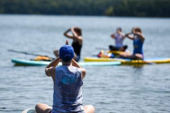 Students in yoga poses on paddleboards on a lake