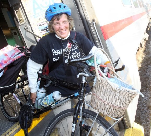 Sally Robertson smiling on bike, wearing library tshirt